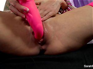 Sarah Jessie pulverizes herself with a pinkish toy